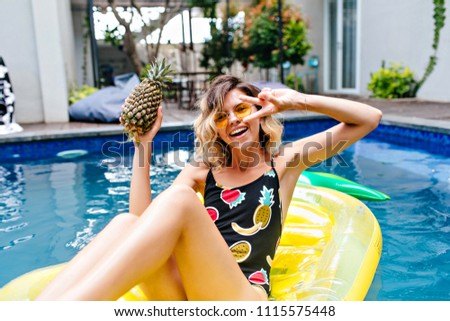 Stock Photo Fascinating girl with tattoo posing with peace sign in pool. Portrait of lovable tanned female model holding pineapple and fooling around.