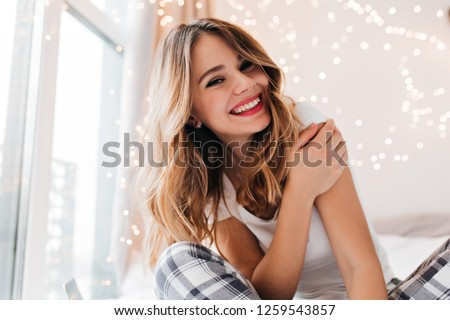 Fascinating white girl with light makeup posing in her room. Glad young woman sitting beside window at home and smiling.