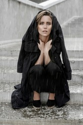 fashion. A young girl walks down the street in the summer in black overalls and a shirt. Graceful woman with a short haircut in a stylish summer dress, makeup. gorgeous sexy woman in the rain