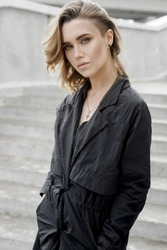 fashion. A young girl walks down the street in the summer in black overalls and a shirt. Graceful woman with a short haircut in a stylish summer dress, makeup. gorgeous sexy woman