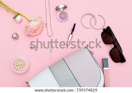 Fashion accessories, cosmetics and handback on a pink background. Flat lay
