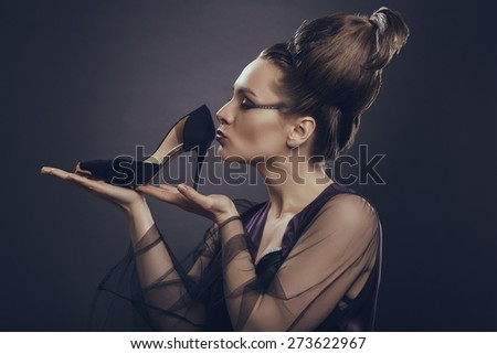 Fashion addicted sensual woman gently holding and kissing her new high heel shoe over dark background. Fashion and shopping addiction concept.