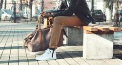 Fashion african man holding bag sitting on  bench in city park close up, male accessory