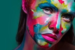Fashion and creative makeup, young beautiful woman abstract face art, portrait on a turquoise background.
