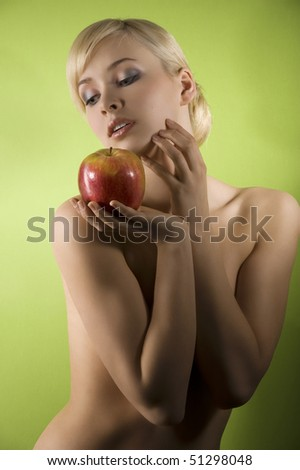fashion and glamour shot of a dreaming nude young woman with red apple on green background