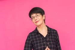 Fashion and people concept - Portrait of middle-aged woman in glasses with short hair standing on pink background