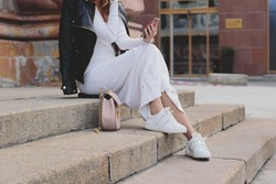 Fashion and style foxy girl in white knitted dress and white sneakers holding her mobile phone and taking self portraits