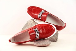 Fashion and stylist concept. Red loafers, boots or moccasins on a stone podium on a neutral background with place for text. Ideal for illustrating articles