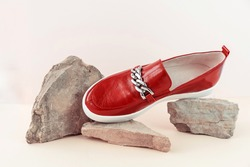 Fashion and stylist concept. Red loafers, boots or moccasins on a stone trending catwalk on a neutral background with place for text. Ideal for your article