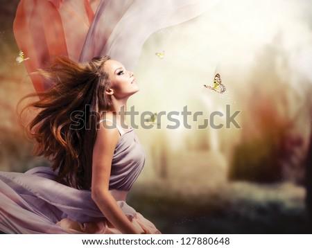 Fashion Art Beauty Portrait. Beautiful Girl in Fantasy Mystical and Magical Spring Garden. Model Woman wearing Long Chiffon dress