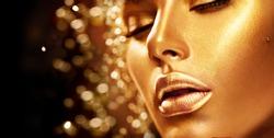 Fashion art Golden skin Woman face portrait closeup. Beauty gold eyes, Lips and Skin. Model girl. Glamour shiny professional makeup