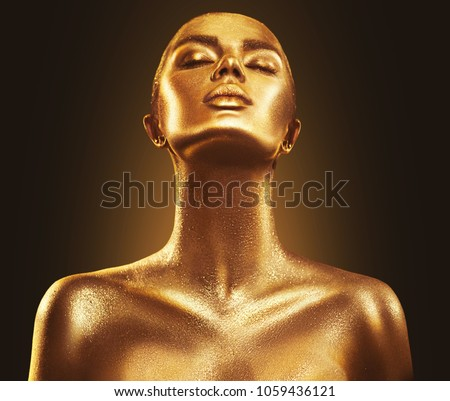 Fashion art Golden skin Woman face portrait closeup. Model girl with holiday golden Glamour shiny professional makeup. Gold jewellery, jewelry, accessories. Beauty gold metallic body, Lips and Skin.  #1059436121