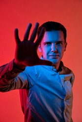 Fashion art portrait of emotional young guy, blocking face with hand. Red and blue light color. Multicolor.