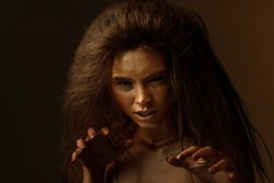 Fashion art portrait of female actress plays the role of a cat, lion or tiger. concept of wild animal inside every woman. beaty woman with gold metallic body and hair on dark background.