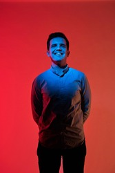 Fashion art portrait of smiling young guy face, holds hands behind his back. Red and blue light color.