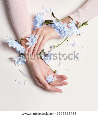 Fashion art portrait woman in summer dress and flowers in her hand with a bright contrasting makeup. Creative beauty photo girls sitting at table on a contrasting pink background with colored shadows