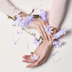 Fashion art skin care of hands and blue flowers in hands of women. Creative beauty photo hands, sitting at table on a contrasting pink background with colored shadows. Cosmetics for hands anti wrinkle