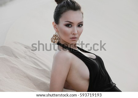 Fashion asian sexy woman model posing in luxury dress in desert