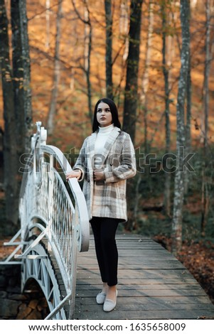 Fashion autumn portrait of stylish model woman, posing. Woman posing in park in warm coat, autumn fashion trend. Beautiful young teen girl