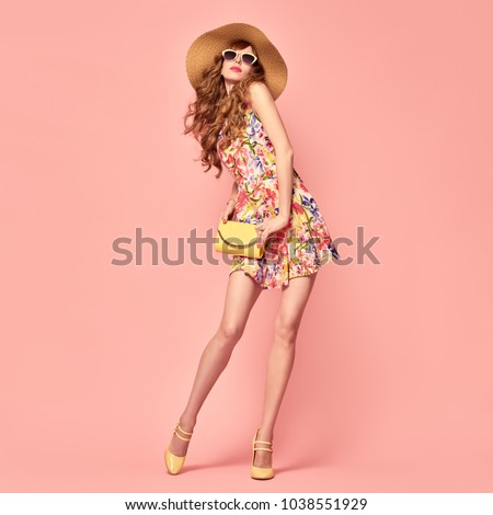 Fashion. Beautiful Lady in floral summer dress, long hair, hat smiling. Playful woman with fashionable handbag on pink. Model girl with trendy wavy hairstyle, summertime fashion outfit.