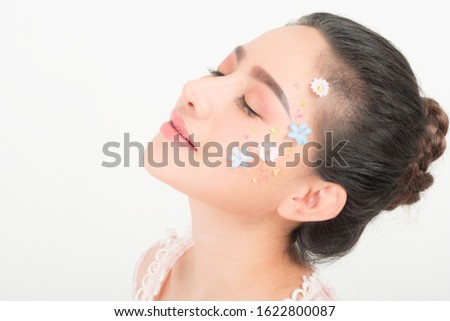 Fashion beauty makeup with flowers on face beautiful woman.
