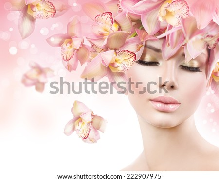 Fashion Beauty Model Girl with Orchid Flowers Hair. Spa woman. Bride. Perfect Creative Make up and Hair Style. Hairstyle. Nude makeup. Bouquet of Beautiful Flowers on lady\'s head