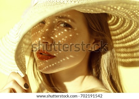 Fashion beauty portrait of a woman in a hat, a shadow falls on a woman from a hat and looking at camera. Yellow background, outdoor #702191542