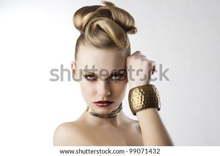 fashion beauty portrait of blond young cute girl with creative hair style and leopard make up, she is in front of the camera, looks in to the lens and has the right hand near the left part of the face
