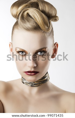 fashion beauty portrait of blond young cute girl with creative hair style and leopard make up, she is in front of the camera and looks in to the lens