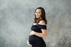 Fashion beauty portrait of happy pregnant woman in black dress on gray background