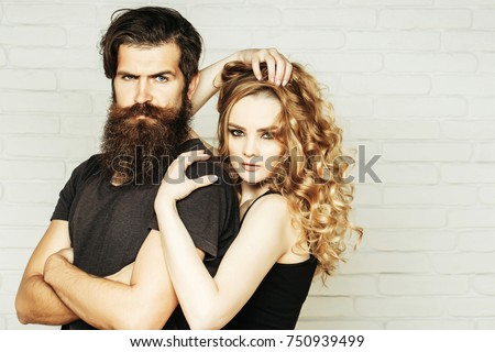 Fashion, beauty, style concept. Girl and bearded hipster. Hipsterism, subculture, trend. Man with beard and woman with long blond hair. Couple in love hug on white brick wall.