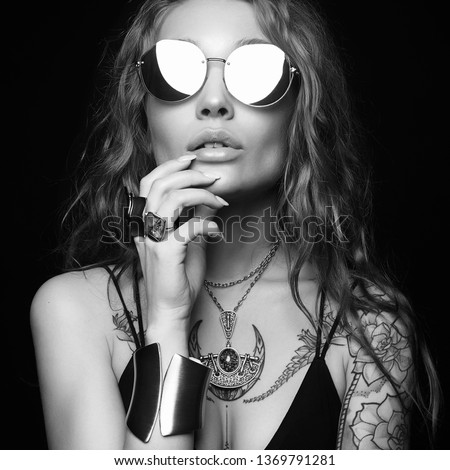fashion black and white portrait of Beautiful sexy woman with tattoo. beauty tattooed girl in sunglasses and jewelry