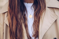 fashion blogger outfit details. fashionable woman wearing a beige trench coat, white t shirt, choker necklace and a round gold chain necklace. detail of a perfect fall fashion outfit.