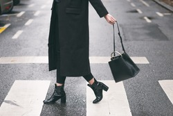 fashion blogger outfit details. fashionable woman wearing a black oversized coat, black jeans, black ankle shoes a black trendy handbag. detail of a perfect fall fashion outfit.