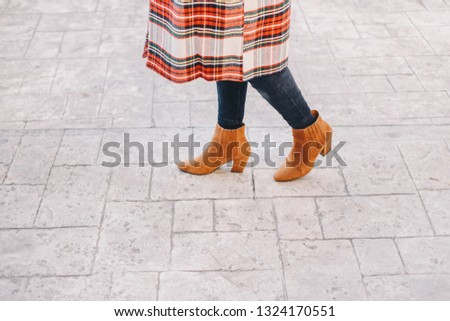 Fashion blogger outfit details. Fashionable woman wearing a plaid overcoat, black jeans and camel ankle shoes. Detail of a perfect fall or winter fashion outfit.