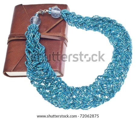 Fashion Blogging Concept with Teal Necklace and Brown Journal on White.