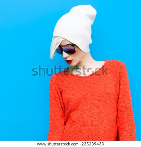 Fashion Blond Girl with trendy Cap and Sunglasses on a blue background