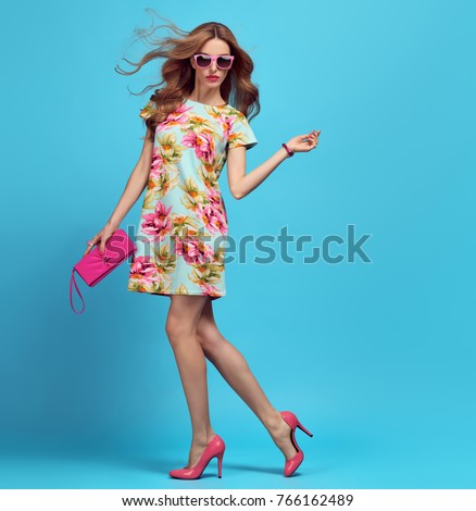Fashion. Blond Woman. Young beauty Lady in Floral Dress, Trendy Hairstyle, fashionable Pink Heels, Glamour Clutch. Playful Girl, Spring Summer Outfit