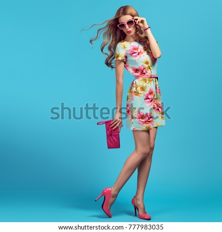 Fashion. Blond Woman. Young beauty Lady in Floral Dress, Trendy Hairstyle, Pink Heels, Glamour Clutch. Playful Girl, Spring Summer Outfit - Shutterstock ID 777983035
