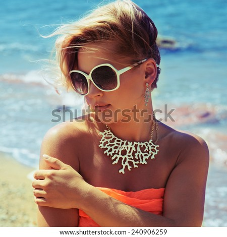 Fashion blonde female in vacation. Posing with cute summer style, pare on bikini, sunglasses and big white necklace. Photo with instagram style filters - Shutterstock ID 240906259