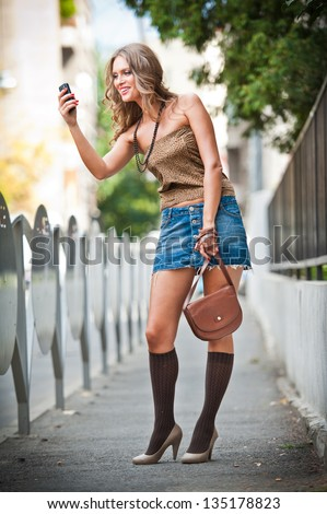 fashion blonde girl with short skirt at playing with mobile phone.Young attractive woman talking on a cell phone in a  street.happy young woman play by mobile phone on the street