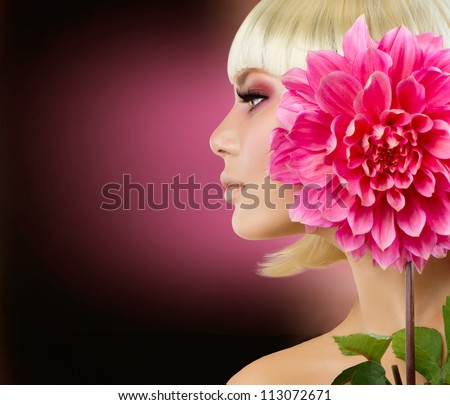 Fashion Blonde Woman with Dahlia Flower. Blond Hair. Hairstyle. Haircut. Makeup