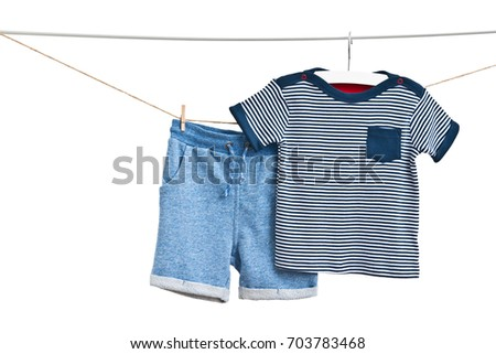 Fashion blue baby-boy shorts and T-shirt (marine style) hanging on a rope isolated on white background/ Baby clothes/ Close-up. #703783468