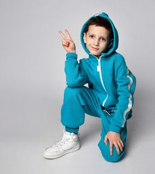 Fashion boy child in warm sportswear suit kneeing gesturing victory looking at camera. Male kid advertising sportive outerwear clothing. Sportive fashionable outfit. Studio shot portrait
