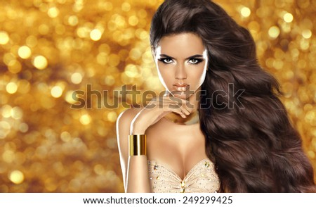 Fashion brunette girl with Long wavy hair, beauty makeup, luxury jewelry. Beautiful attractive young woman in dress posing over holiday lights glitter background.