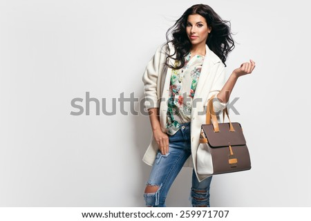 Fashion brunette model in nice clothes posing in the studio. Wearing coat, handbag, ripped jeans