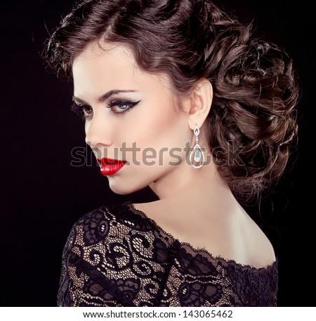 Fashion Brunette Model Portrait. Jewelry and Hairstyle. Elegant lady Isolated on black background.