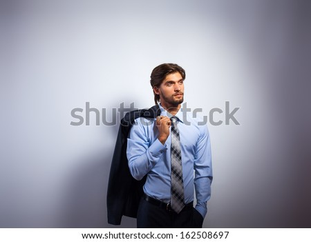 Fashion business man, Handsome male model blue shirt and tie suit look side to copy space, young businessman over gray background