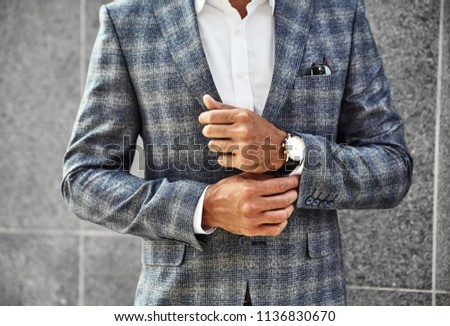 Fashion businessman model dressed in elegant checkered suit posing near gray wall on street background. Metrosexual with luxury watch on wrist Stock photo ©