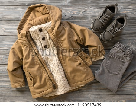 Fashion children's clothing, shoes (knit sweater, hooded canvas jacket, jeans, suede boots). Outfit for little boy. Winter, autumn collection. Organic cotton. Top view, flat lay